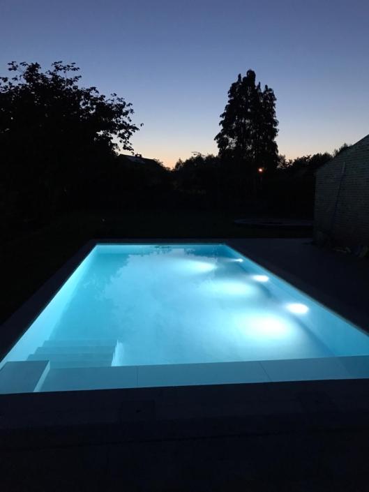 Zwembad bij valavond in een tuin met trappen en verlichting